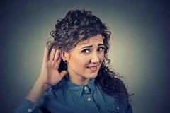 Несчастный крепко женщины слуха устанавливая руку на ухе спрашивая, что кто-то поговорило вверх стоковое изображение rf