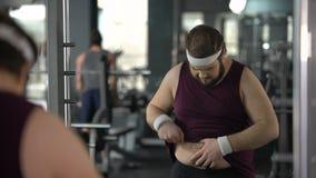 Несчастный полный человек смотря его отражение зеркала в спортзале, диете и спорте сток-видео