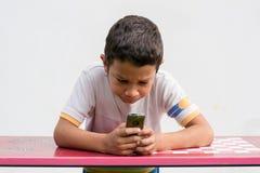 Несчастный ребенок отправляя СМС на телефоне Стоковое фото RF