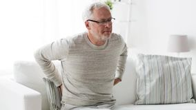 Несчастный старший человек страдая от backache дома 103 акции видеоматериалы