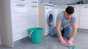 Несчастный уставший человек в резиновых перчатках моет пол в кухне и взгляды на камере в конце сток-видео