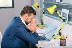 Несчастный человек, сидя на столе в офисе, с разочарованным пристальным взглядом и льнет к его стороне indoors стоковые изображения