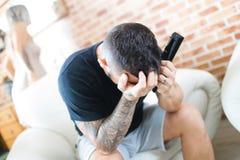 Несчастный человек смотря телевидение, сторону в руках стоковые фото