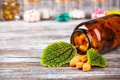Нетрадиционная медицина в стеклянных тарах с зелеными листьями Стоковое фото RF