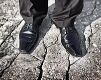 Ноги бизнесмена стоя на треснутой земле Стоковая Фотография RF