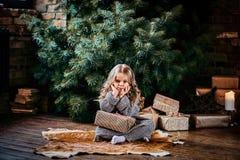 Неудовлетворенная маленькая девочка с белокурым вьющиеся волосы нося теплый свитер сидя на поле окруженном подарками рядом с стоковая фотография rf