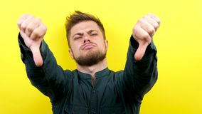 Неудовлетворенный кавказский человек показывая большие пальцы руки вниз на желтой предпосылке сток-видео