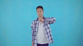 Неудовлетворенный молодой азиатский человек показывает знак нелюбов на голубой предпосылке видеоматериал