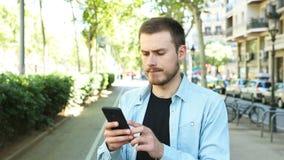 Неудовлетворенный человек использует телефон с большим пальцем руки вниз акции видеоматериалы