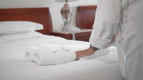 Неузнаваемая взрослая старшая женщина кладет белое полотенце рядом с белым купальным халатом на кровать в гостиничный номер ( видеоматериал