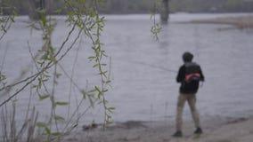 Неузнаваемый молодой уверенный рыболов в рыбной ловле раннего утра закручивая в реке около города Рыболовная удочка и a акции видеоматериалы