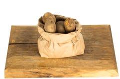 Неумытые картошки в бумажной сумке islated на белизне Стоковая Фотография RF