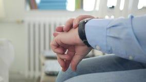 Неусидчивый человек делает нервные жесты рук посмотреть к контрольному времени наручных часов видеоматериал