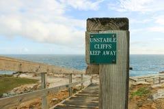 Неустойчивые скалы держат отсутствующий предупредительный знак на древесине Стоковое фото RF