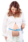 Неудовлетворенная беременная женщина измеряет живот Стоковые Фото