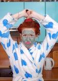Неудовлетворенная домохозяйка в халате о curlers волос и в маске глины поднимает сковороду в кухне Стоковое Изображение