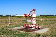 Нефтяная скважина в поле, покрашенном в белом и красной Масло с современным оборудованием Стоковое Изображение RF