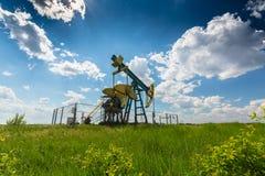 Нефтяная скважина нефти и газ профилированная на голубом небе с облаками кумулюса, в Европе Стоковые Фотографии RF