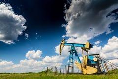 Нефтяная скважина нефти и газ профилированная на голубом небе с облаками кумулюса, в Европе Стоковое Фото