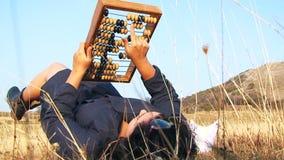 Нечетная женщина в черный играть с абакусом на природе видеоматериал
