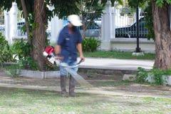 Неясное изображение человека кося парк травы публично Стоковая Фотография RF