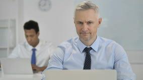 Не, бизнесмен волос серого цвета тряся голову для того чтобы отвергнуть план