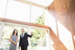 Недвижимый агент показывая молодой женщине новый дом стоковое фото rf