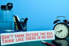 Не думайте вне коробки, думайте как там никакое планирование коробки на предпосылке таблицы деятельности с канцелярские товарами стоковые изображения