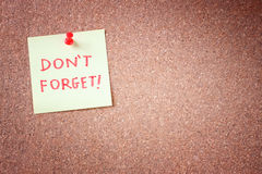 Не забудьте или не забудьте напоминание, написанное на желтом стикере на бюллетене пробочки или доске для сообщений. стоковые изображения