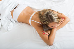 нижнее белье женщины нося представляя на кровати Стоковое Изображение RF