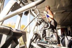 Нижний взгляд белокурой женщины в фитнес-клубе, езда на orbitrack Стоковое фото RF