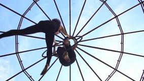 Нижний взгляд как атлетические женщины делает фокусы в кольце для воздушной акробатики сток-видео
