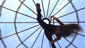 Нижний взгляд как девушка делает висеть шпагата вверх ногами на кольце для воздушной акробатики видеоматериал
