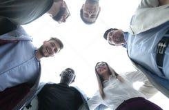 Нижний взгляд команда дела стоит совместно, формирующ круг стоковые фото