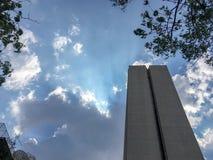 Нижний взгляд офисного здания на небе облаков голубом с предпосылкой солнечного света стоковые изображения