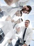 Нижний взгляд счастливая команда дела читая подписанный контракт стоковые изображения