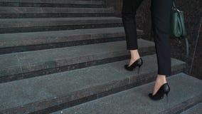 Нижняя часть бизнес-леди в официально костюме идя вверх по внешней лестнице видеоматериал