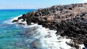 Низкая муха вдоль пляжа Крита, голубых волн моря разбивая в скалистое побережье, Грецию сток-видео