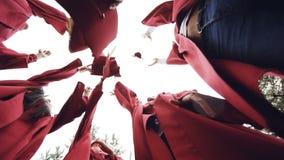Низкая угловая съемка девушек и студентов парней градуируя бросая миномет-доски в небе и смеяться над праздновать видеоматериал
