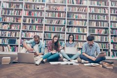 Низкая угловая съемка 4 международных ухищренных студентов книгоедов i стоковая фотография rf
