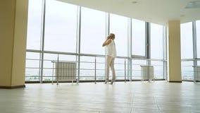 Низкая угловая съемка молодой белокурой женщины говоря по телефону в пустом лобби офиса сток-видео