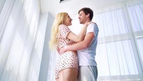 Низкая угловая съемка молодых пар в носке сна обнимая около curtained окна сток-видео