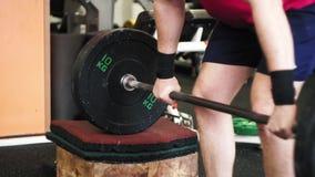 Низкая угловая съемка на ногах человека делающ сидения на корточках с олимпийским баром сток-видео