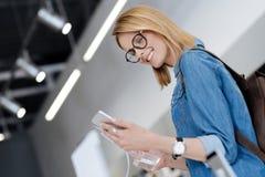 Низкая угловая съемка положительной женщины смотря мобильный телефон шаблона Стоковые Фото