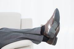 Низкий взгляд со стороны раздела бизнесмена отдыхая на софе Стоковая Фотография RF