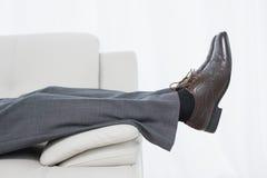 Низкий взгляд со стороны раздела бизнесмена отдыхая на софе Стоковые Изображения RF