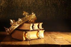 низкий ключ красивых ферзя/кроны короля на старых книгах Фильтрованный год сбора винограда период фантазии средневековый Стоковая Фотография RF
