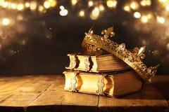 низкий ключ красивых ферзя/кроны короля на старых книгах Фильтрованный год сбора винограда период фантазии средневековый стоковое изображение