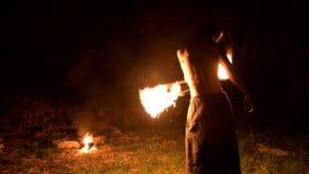 Низкий ключ Молодой мужчина с длинными волосами и нагим торсом поворачивает горящий факел outdoors на черном видео ночи медленном сток-видео