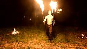 Низкий ключ Молодой мужчина с длинными волосами и нагим торсом поворачивает горящий факел outdoors на черном видео ночи медленном акции видеоматериалы